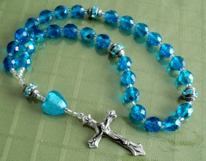 This is a Protestant rosary. Unlike a Catholic Rosary, there are 7 beads (weeks) and 4 weeks between the cruciform beads.,. The Catholic Rosary has 10 beads (decades) and 5 decades, between the cruciform beads. A crucifix or cross ia acceptable on an Anglican Rosary (cross is more common)